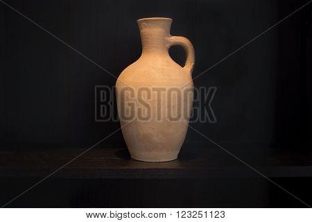Terracotta caraffe earthenware household item with handle handmade on a dark shelf isolated on black.