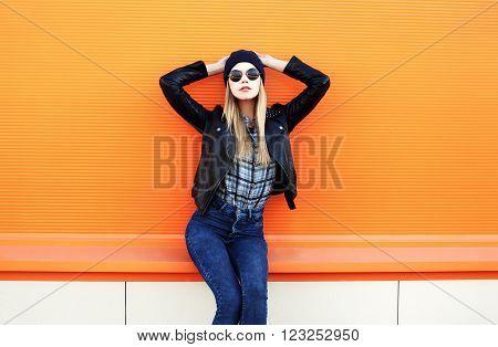 Fashion Pretty Blonde Woman In Rock Black Style Posing Over Orange Background