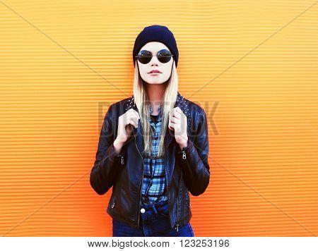 Portrait Fashion Blonde Woman In Rock Black Style Over Orange Background