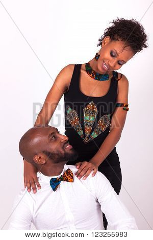 Happy African American couple wearing traditional clothes over grey background