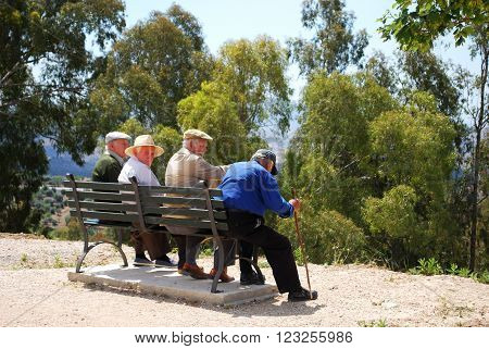 PERIANA, SPAIN - JUNE 1, 2008 - Four elderly Spanish men sitting on bench Periana Costa del Sol Malaga Province Andalusia Spain Western Europe, June 1, 2008.