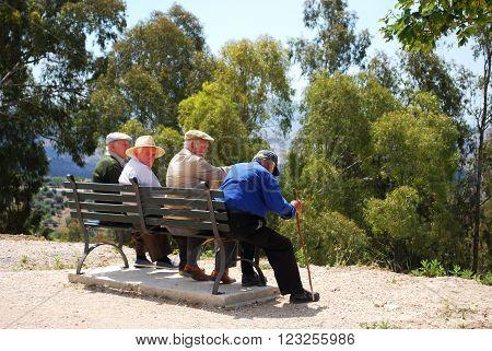 PERIANA, SPAIN - JUNE 1, 2008 - Four elderly Spanish men sitting on bench Periana Costa del Sol Malaga Province Andalusia Spain Western Europe, June 1, 2008.