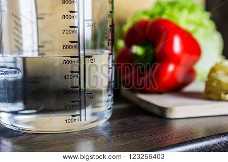 500Ccm / 1/2 Liter / 500Ml Of Water In A Measuring Cup On A Kitchen Counter With Food