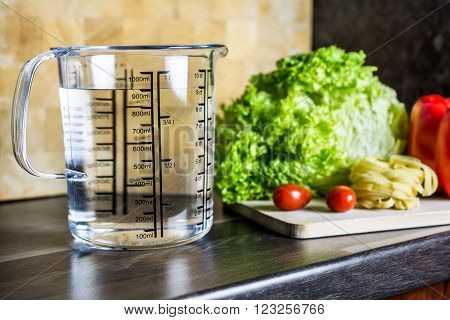 900ccm / 900ml Of Water In A Measuring Cup On A Kitchen Counter With Food
