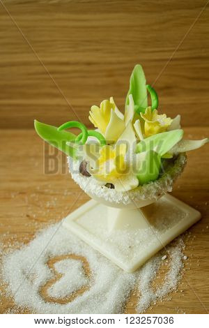 Sweet dessert of white chocolate with decorations of mastic of white flowers.
