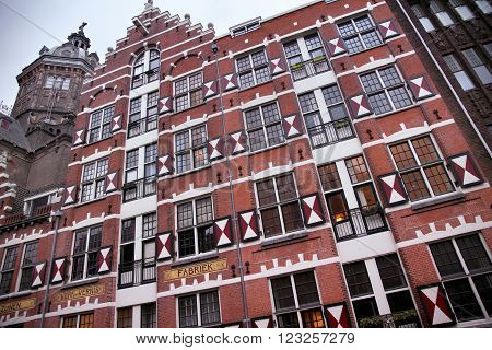 AMSTERDAM; THE NETHERLANDS - AUGUST 18; 2015: View on Oudezijds Kolk canal in Amsterdam, building Verf en Vernis Fabriek H.Vettewinke in Amsterdam. Amsterdam is capital of the Netherlands on August 18; 2015.