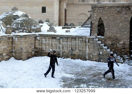 BAKU, AZERBAIJAN - JANUARY 31 2014  Throwing snowballs in Baku's Old City, in the capital of Azerbaijan. An unusual snowfall in Baku is the cause of excitement