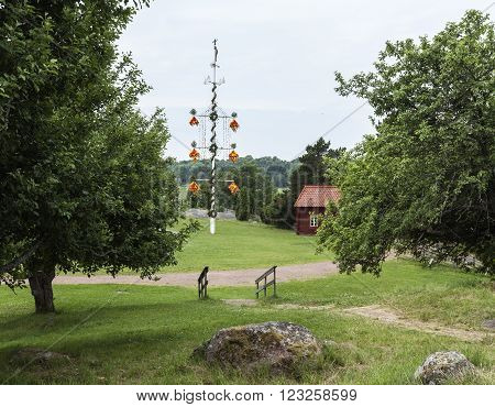 Maypole, midsummer celebrations in Aland Islands. Buildings in the background.