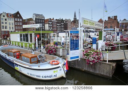 AMSTERDAM; THE NETHERLANDS - AUGUST 16; 2015: Beautiful views of the ancient buildings at the waterside canal and boats Damrak canal in Amsterdam The Netherlands on August 16; 2015.