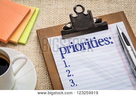 priorities list on clipboard  with a pen, coffee and sticky notes against burlap canvas - office abstract