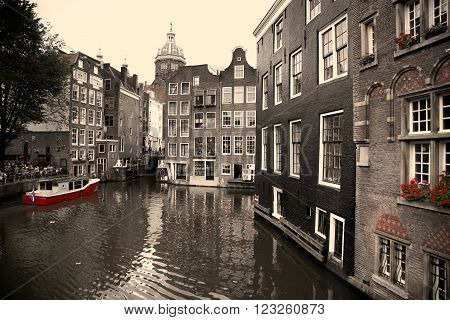 AMSTERDAM THE NETHERLANDS - AUGUST 18 2015: View on Saint Nicholas church or St Nicolaas kerk tower from Armbrug bridge. Street life Canal tourists and boat in Amsterdam. Amsterdam is capital of the Netherlands on August 18 2015.