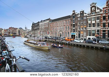 AMSTERDAM, THE NETHERLANDS - AUGUST 19, 2015: View on Rokin from bridge Doelensluis. Street life, Canal, tourists, bicycle and boat in Amsterdam. Amsterdam is capital of the Netherlands on August 19, 2015.