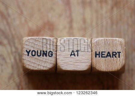 Young at heart printed on three wooden dice against wood grain background