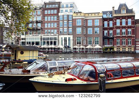 AMSTERDAM THE NETHERLANDS - AUGUST 19 2015: View on Hotel de l'Europe and Amstel street from Halvemaansbrug. Street life Canal bicycle and boat in Amsterdam. Amsterdam is capital of the Netherlands on August 19 2015.