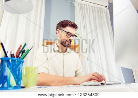 Portrait Of Young Successful Man Working And Typing On Computer