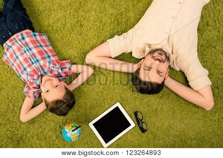 Top View Of Father And Son Lying On Green Carpet With Globe, Tablet And Glasses