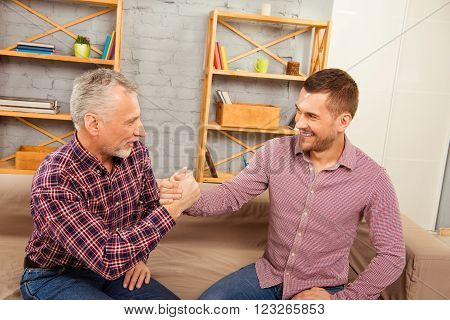 Aged father and his handsome son competing in arm wrestling