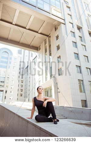 Young attractive minded ballerina sitting on the balusters.