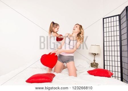 Excited Pretty Mother And Daughter Fighting With Pillows In Bedroom