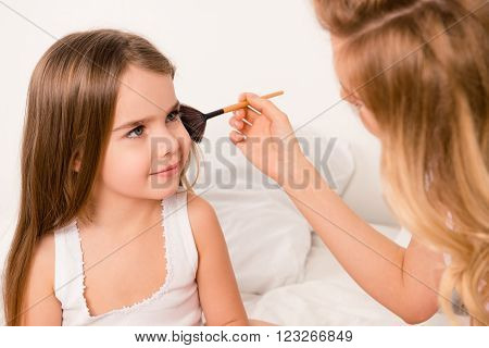 Close Up Portrait Of Woman Doing Maquillage To Her Cute Daughter