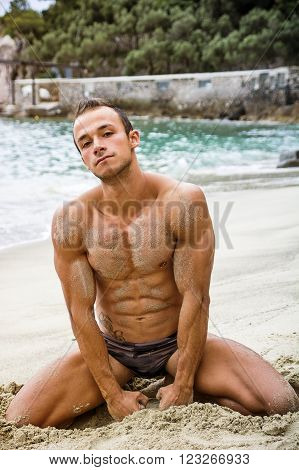 Attractive and fit young bodybuilder in bathing suit kneeling on the beach