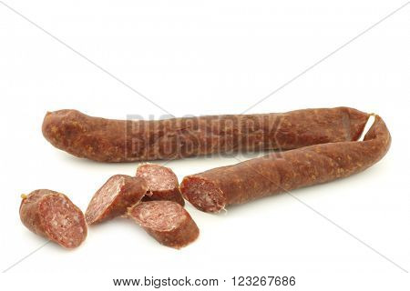 traditional frisian smoked and dried sausages and some cut pieces on a white background