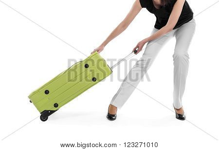 Woman drags a heavy suitcase on a white background.