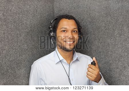 Young man in audiology booth getting his hearing tested