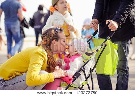 Mom is played with the little girl. The child sits in a wheelchair. A family walk in the spring in the Park. The woman in the yellow jacket. A blurred background.