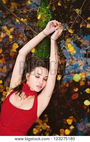portrait of a young white girl with long dark hair and brown eyes in red dress lying on the water with my eyes closed