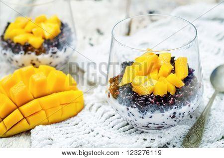 Coconut black rice mango pudding on white wood background.