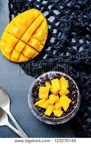 Coconut black rice mango pudding on a black background.