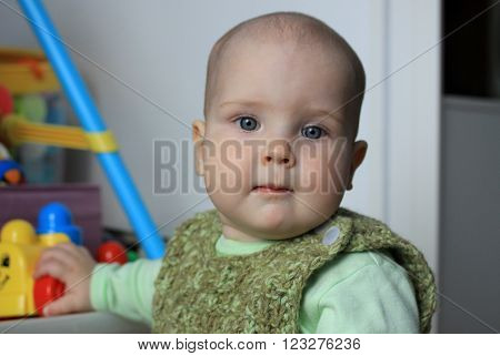 Portrait of a 11-months baby with toys