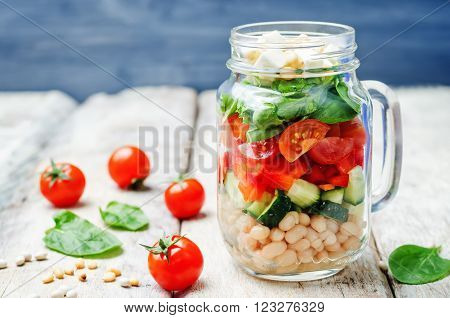 White beans cucumber tomato red pepper feta spinach salad in a jar.