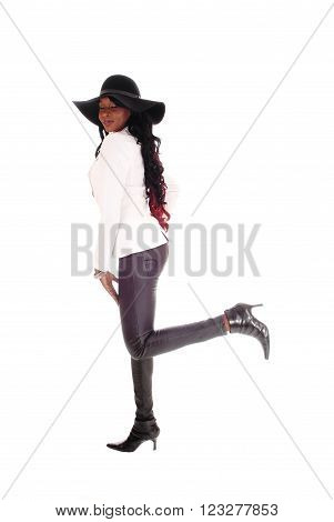 A young slim African American woman in tight leather pants white jacket  and black hat standing isolated for white background.