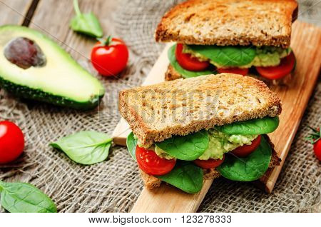 Smashed avocado spinach tomato grilled rye sandwich.