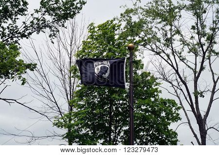 ELWOOD, ILLINOIS / UNITED STATES - MAY 30, 2015: A black POW/MIA Flag flies at the Abraham Lincoln National Cemetery in Elwood, Illinois.