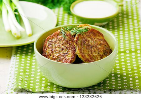 vegetable marrows fritters with sour cream on a green plate. selective focus