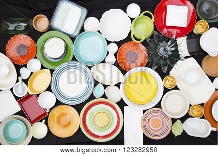 Colorful dishes and utensils on a black background