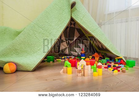 Coloful wooden cubes on floor nearby wigwam