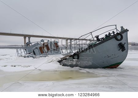 Sunken vessel in a frozen river covered with ice
