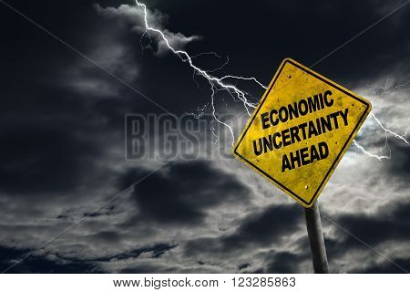 Economic Uncertainty sign against a stormy background with lightning and copy space. Dirty and angled sign adds to the drama.
