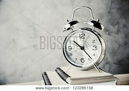 Front view of alarm clock and copybooks on concrete background