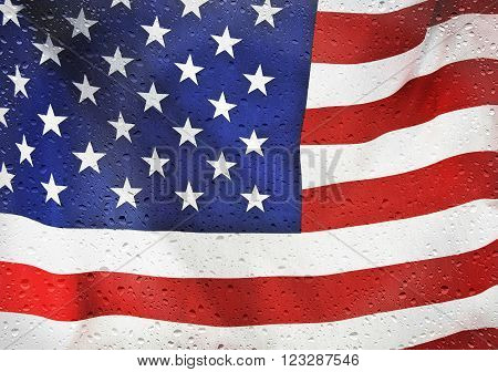 Close up of an American flag with raindrops on windowpane.