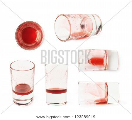 Glass shot with grenadine red syrup leftovers isolated over the white background, set of six different foreshortenings