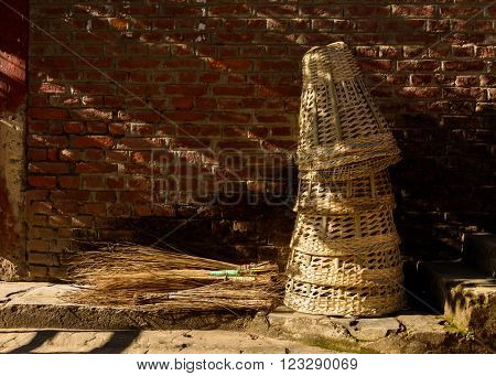 Wicker baskets and brooms against a brick wall in Nepal
