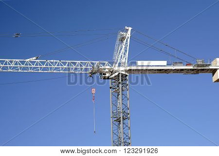 The arm and base of construction crane with a crane hook and a driver's cab.