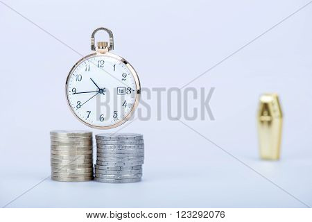 Pocket watch with European currencies and tomb in still life