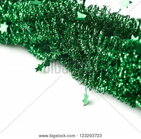 Close-up fragment of the tinsel green garland decorations isolated over the white background as a copyspace backdrop composition