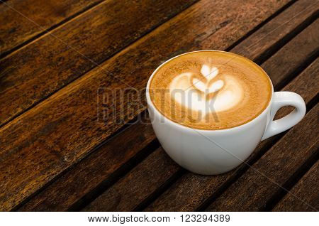 A cup of coffee with heart pattern in a white cup on wooden background.Close up